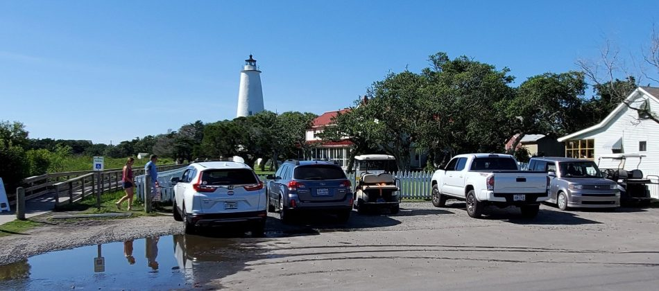Visitors-cars-and-golf-carts-fill-Ocracoke-Light-Station-parking-lot-Friday-afternoon-June-18-2021-edited